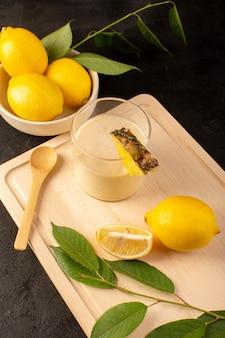 Вид сверху свежий коктейль вкусный прохладительный напиток внутри маленького стакана возле деревянного стола крем с желтыми лимонами на темноте