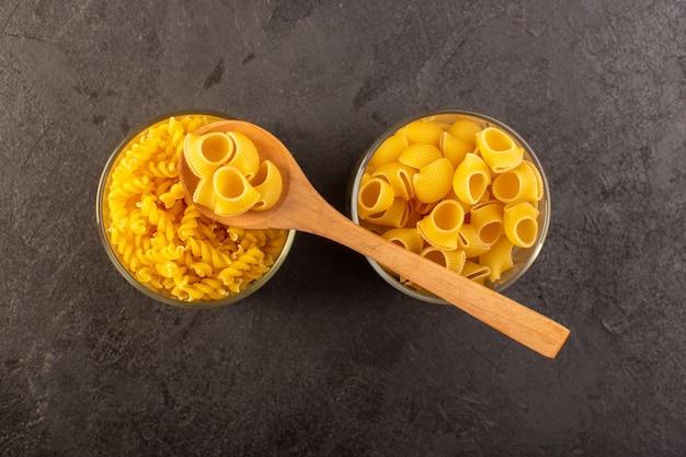 Вид сверху итальянские сухие макароны желтые сырые внутри чаши с ложкой, изолированных на темноте