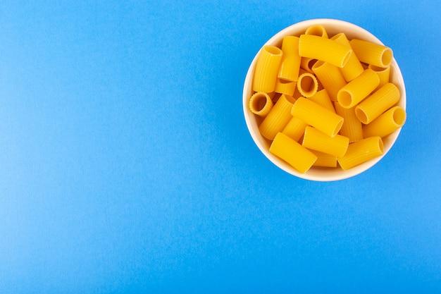 Вид сверху итальянские сухие макароны сформировали маленькие желтые сырые макароны внутри кремового цвета круглой миске, изолированных на синем