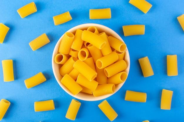 トップビューイタリアの乾燥パスタは青い背景のイタリアのスパゲッティ食品パスタに分離されたクリーム色の丸いボウルの中に少し黄色の生パスタを形成