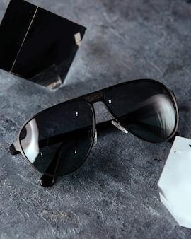 灰色の背景のトップビューモダンな黒のサングラスは、ビジョンメガネエレガンスを分離しました。
