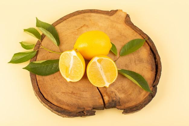 トップビュースライスされたレモンと木製の茶色の机の上の緑の葉と全体がクリーム色の背景の柑橘系の果物の色で新鮮なジューシーなまろやかを分離