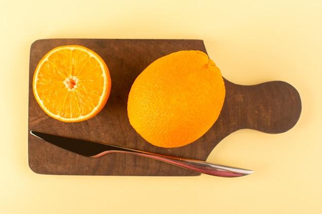 茶色の木製の机とクリーム色の背景の柑橘系のオレンジに銀のナイフと一緒に全体のオレンジの新鮮でジューシーなまろやかさをスライスした平面図