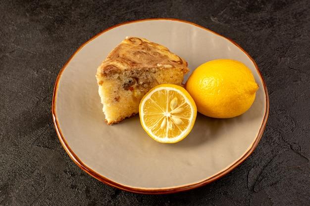 暗い背景の砂糖レモンビスケット焼きに黄色のレモンと一緒にベージュプレート内のおいしい甘いチョコケーキスライスのトップビュー