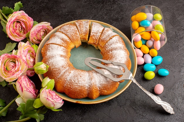 カラフルなキャンディーと一緒に砂糖粉末と平面図甘い丸いケーキプレートと灰色の背景のビスケット砂糖クッキー内の甘いおいしい分離ケーキをスライス