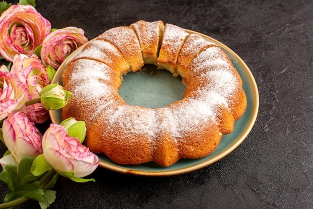 Сладкий круглый торт сверху с сахарной пудрой сверху нарезанный сладкий вкусный изолированный внутри тарелки вместе с цветами и серым фоном печенья печенья сахара