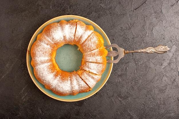 上から見た甘い丸いケーキと砂糖粉の上にスライスした甘いおいしいプレートと灰色の背景ビスケット砂糖クッキーの内側の分離