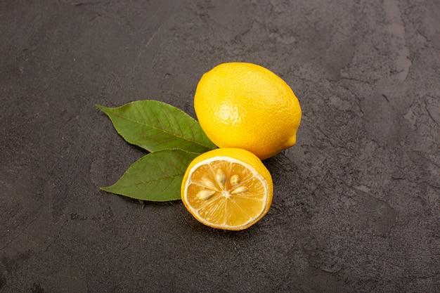 トップビュー黄色の新鮮なレモンのまろやかでジューシーな全体と暗い背景果物柑橘系の色の緑の葉でスライス