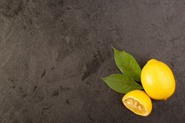 Вид сверху желтый свежий лимон сочный и сочный целый и нарезанный зелеными листьями на темном фоне фруктов цитрусового цвета