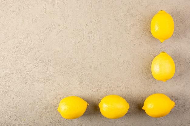 トップビュー黄色の新鮮なレモン熟したまろやかでジューシーなグレーの背景果物柑橘系の色に並んで
