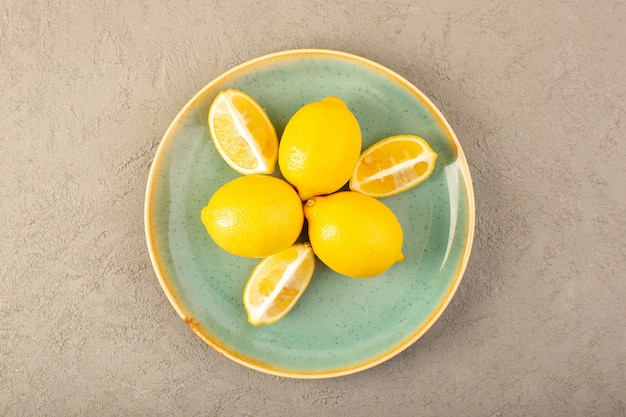 トップビュー黄色の新鮮なレモン熟したまろやかでジューシーな全体と灰色の背景の果物の柑橘系の色の緑のプレート内でスライス