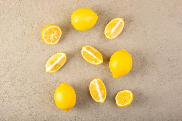 平面図黄色の新鮮なレモン熟したまろやかでジューシーな全体とスライスされた灰色の背景の果物の柑橘系の色の裏地