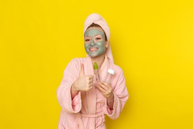 笑みを浮かべてスプレーを保持しているピンクのバスローブで正面の若い美しい女性