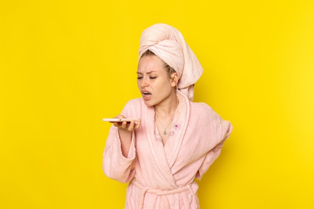 ボイスメッセージを送信するピンクのバスローブの正面の若い美しい女性