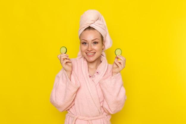 笑顔とキュウリのスライスを保持しているピンクのバスローブで正面の若い美しい女性