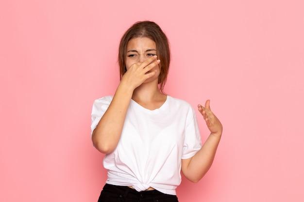 彼女の鼻を覆う白いシャツの正面の若い美しい女性