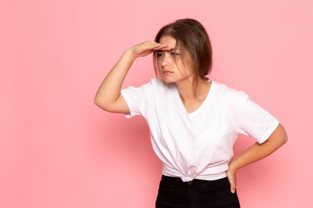 ポーズと遠くを見ている白いシャツの正面の若い美しい女性