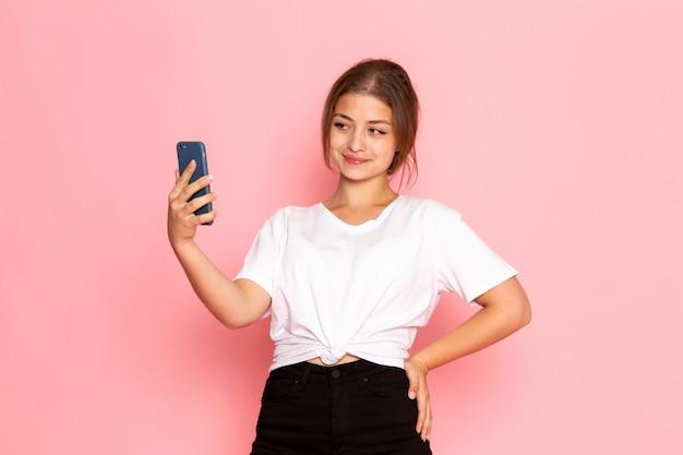 面白い表情でポーズをとって携帯電話を保持している白いシャツの正面の若い美しい女性