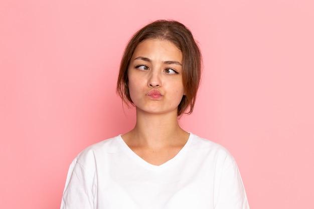 面白い表情でポーズをとって白いシャツの正面の若い美しい女性