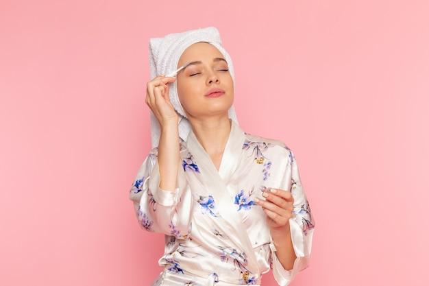 化粧をしているバスローブの正面の若い美しい女性