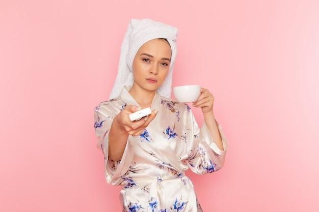 コーヒーを飲みながらエアコンをオフにするバスローブの正面の若い美しい女性