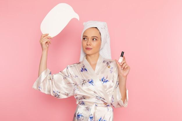 白い看板とマニキュアを保持しているバスローブで正面の若い美しい女性