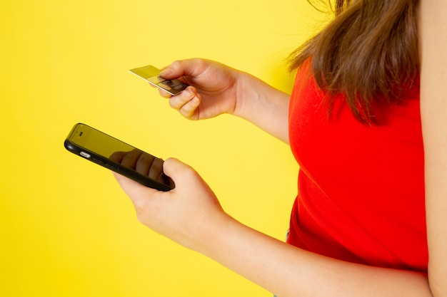 赤いシャツとブルージーンズの電話入力コードを保持している正面の若い美しい女性