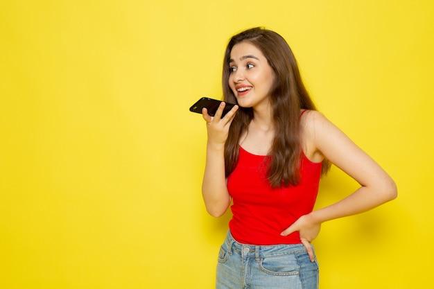 赤いシャツとブルージーンズのポーズとボイスメッセージの送信で正面の若い美しい女性