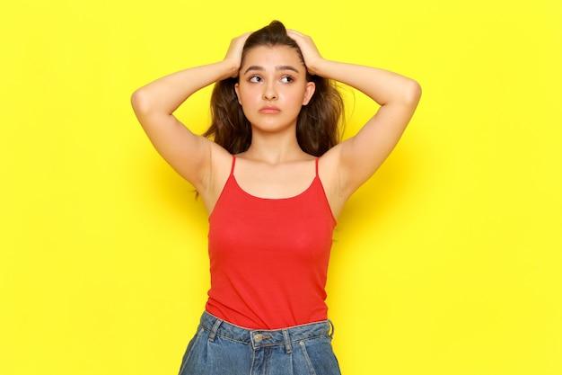 赤いシャツとブルージーンズが彼女の髪に触れるポーズで正面の若い美しい女性