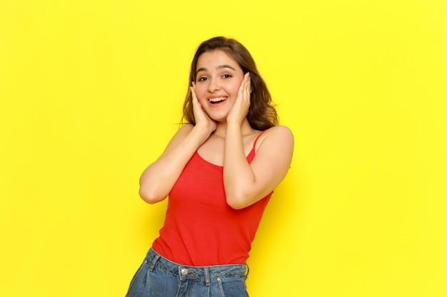 赤いシャツとブルージーンズが喜んで興奮してポーズでポーズをとって正面の若い美しい女性