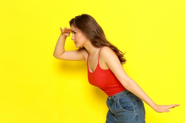 赤いシャツとジーパンが式を検索してポーズで正面の若い美しい女性