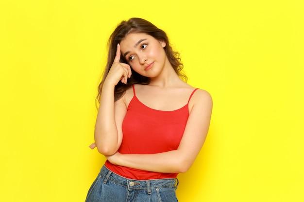 赤いシャツとジーパンが思考の表情でポーズをとって正面の若い美しい女性