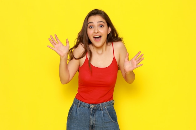 興奮した表情で赤いシャツとジーパンで正面の若い美しい女性