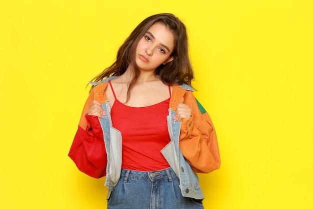 Вид спереди молодой красивой леди в красном пиджаке и синих джинсах со скучающим выражением лица