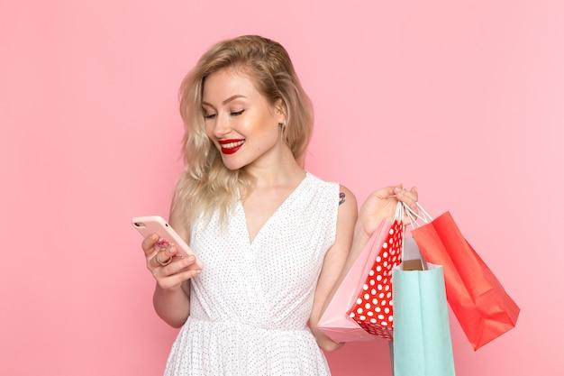 Вид спереди молодая красивая дама в белом платье, держа пакеты с покупками и с телефоном с улыбкой на лице