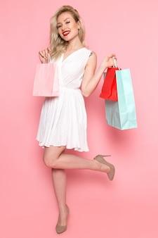 ショッピングパッケージを保持している白いドレスの正面の若い美しい女性