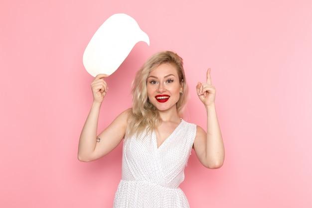 白い看板を持っている白いドレスの正面の若い美しい女性