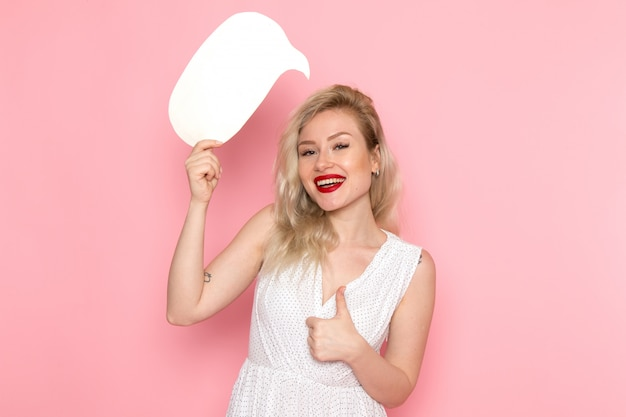 彼女の顔に笑顔で白い看板を持っている白いドレスの正面の若い美しい女性