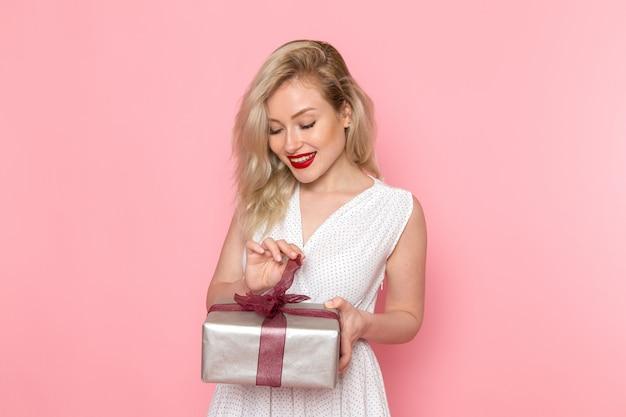 彼女の顔に笑顔でプレゼントボックスを開く白いドレスの正面の若い美しい女性
