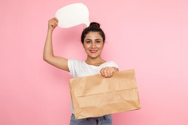 Вид спереди молодая женщина в белой футболке и синих джинсах держит белый знак и пакет