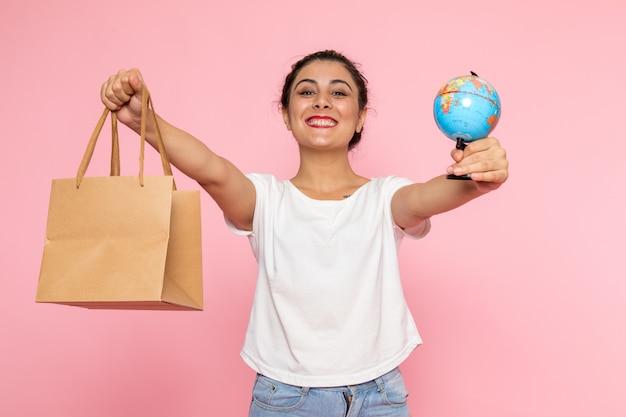 Вид спереди молодая женщина в белой футболке и синих джинсах позирует с улыбкой, держа маленький глобус и пакет