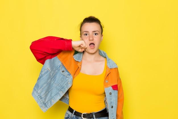 黄色のシャツのカラフルなジャケットとジーパンで彼女の顔を打つ正面の若い女性