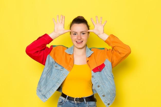 黄色のシャツのカラフルなジャケットとブルージーンズの面白いポーズで正面の若い女性