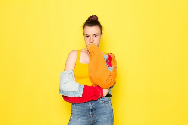 黄色いシャツのカラフルなジャケットとブルージーンズのポーズだけで正面の若い女性