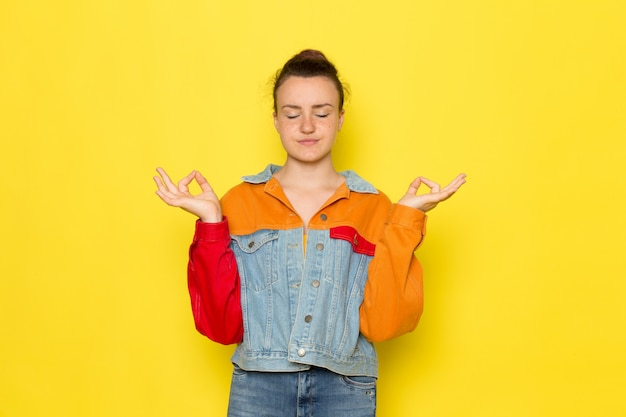 黄色いシャツのカラフルなジャケットとブルージーンズの瞑想で正面の若い女性