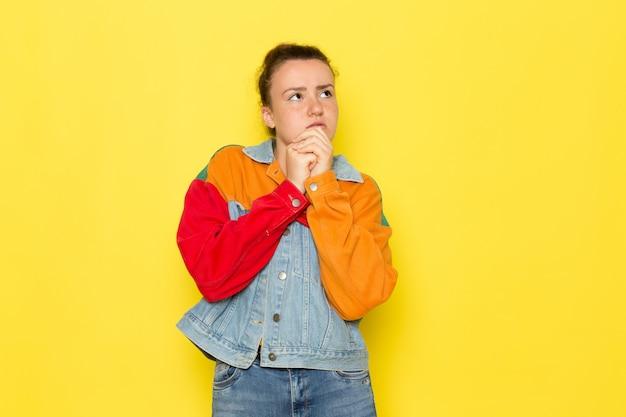 黄色いシャツのカラフルなジャケットとジーパンで正面の若い女性