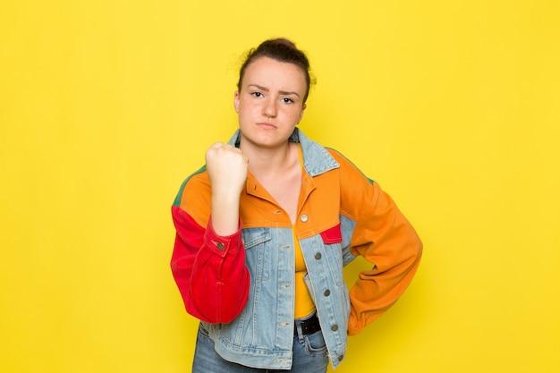 Вид спереди молодая женщина в желтой рубашке красочной куртке и синих джинсах позирует и показывая ее кулак