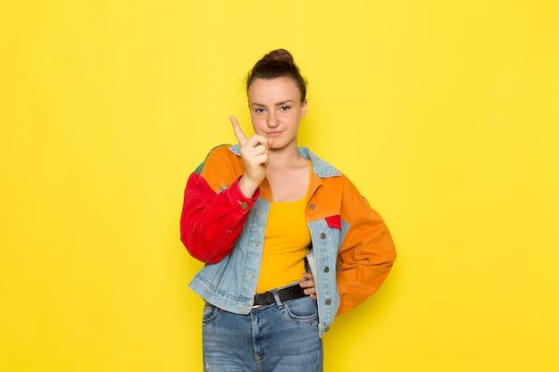 黄色いシャツのカラフルなジャケットとポーズと脅迫のブルージーンズの正面の若い女性