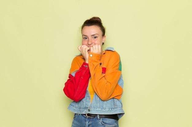 黄色のシャツのカラフルなジャケットとブルージーンズのポーズで正面の若い女性