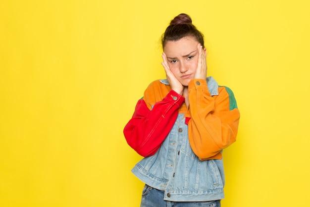 黄色のシャツのカラフルなジャケットと落ち込んだ表情でポーズをとってブルージーンズの正面の若い女性